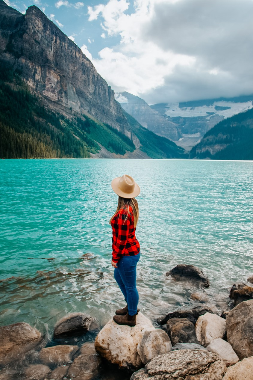 A woman standing in front of a blue lake, wearing a hat, red plaid shirt and blue jeans and looking towards the mountains in the background.