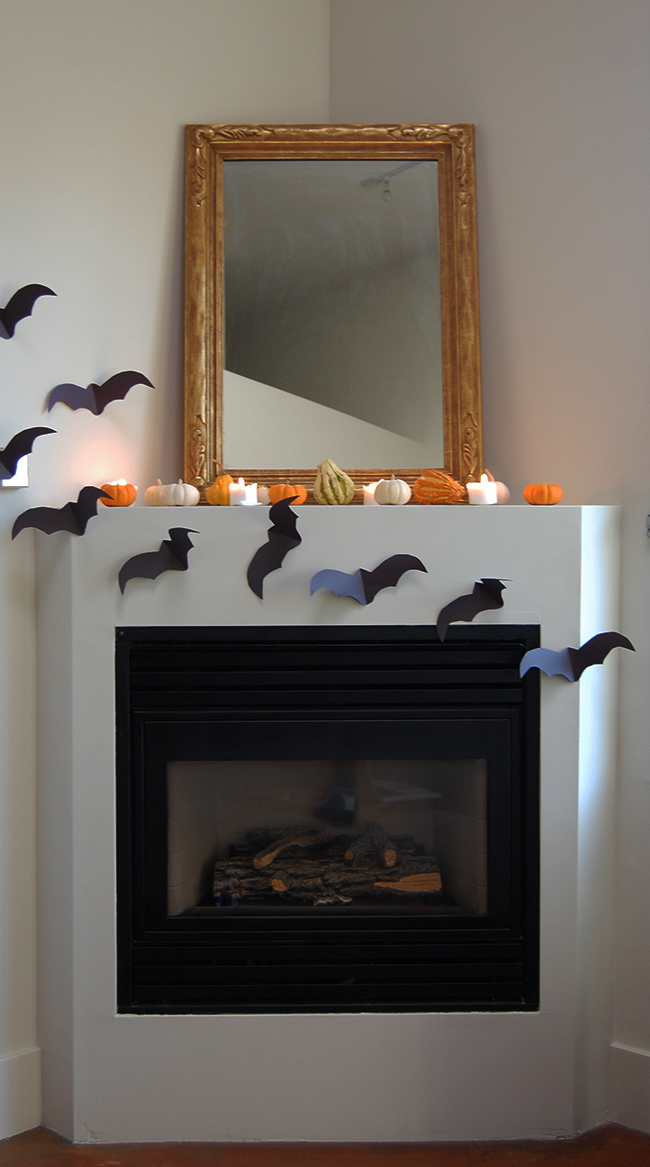 minimalist halloween decor and halloween mantle using pumpkins, candles, and construction paper bats