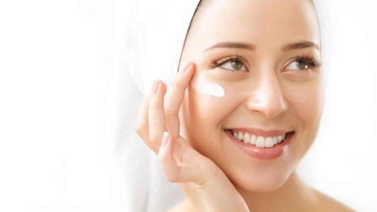 mujer aplicandose crema para el acne