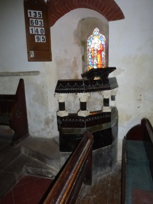 The rather fine serpentine pulpit with window to shine a light on the preacher's notes