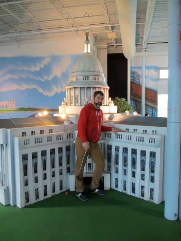 Mr. Tee poses next to a mini version of the State Capitol