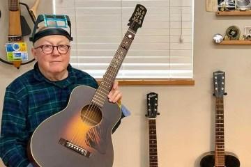 Guitar repairman Dan Erlewine holding an acoustic guitar