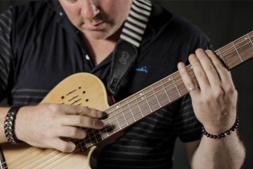 Jeff Gunn close up demonstrating how to play harmonics on acoustic guitar neck