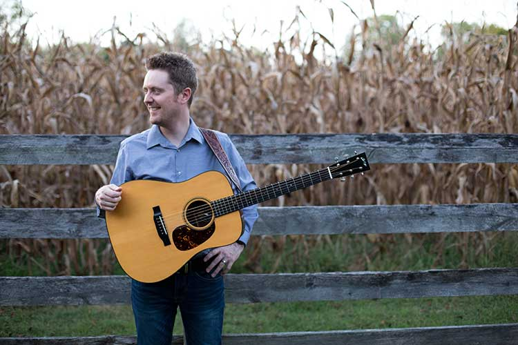 Nashville guitarist Jake Workman against a fence with his guitar