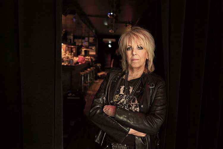 Lucinda Williams with arms crossed standing near a curtain backstage at a music club. Photo by Danny Clinch