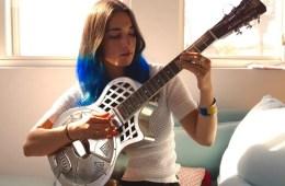 guitarist christina vane playing slide on a resonator guitar