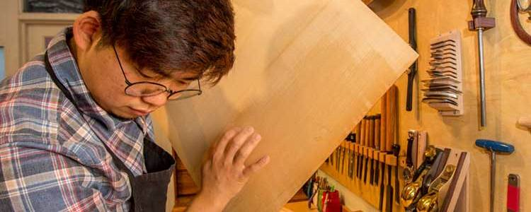 guitar luthier listening to sonic characteristics of tonewood