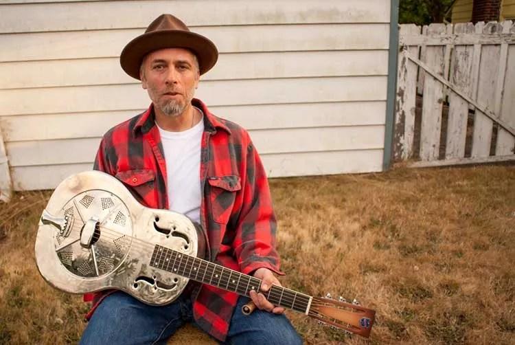 Kelly Joe Phelps sitting outside with his resonator guitar