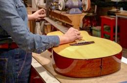 a repair tech making adjustment to an acoustic guitar in a workshop