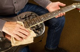 guitarist holds a resonator guitar and cleans it