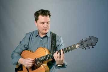 sean mcgowan wearing chambray shirt with gray studio backdrop, demonstrating lesson material on his acoustic guitar