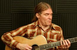 Tim Bertsch demonstrating an exercise from this weekly workout on his acoustic guitar