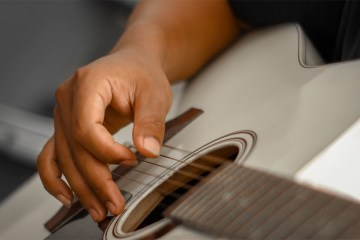 close up of hand picking strings over the soundhole of an acoustic guitar