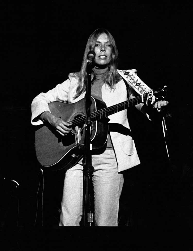 Joni Mitchell onstage with acoustic guitar