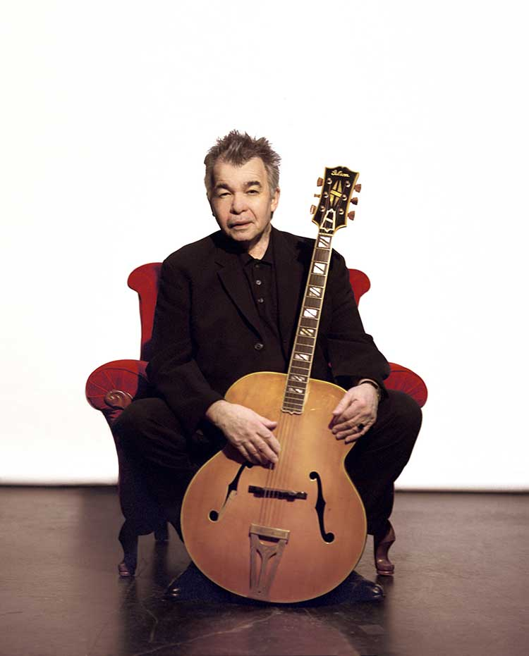 guitarist john prine sitting in a chair with guitar