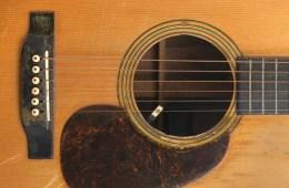 closeup of bridge, soundhole, and pickguard of jerry garcia martin D-28 acoustic guitar