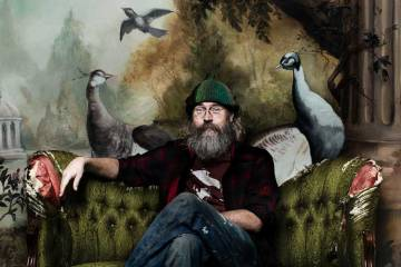 Charlie Parr sitting on couch with birds