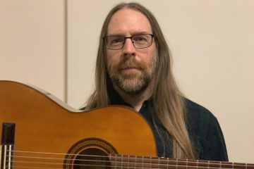 Guitarist Mick Barr with acoustic guitar