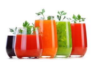 Glasses with fresh vegetable juices on white