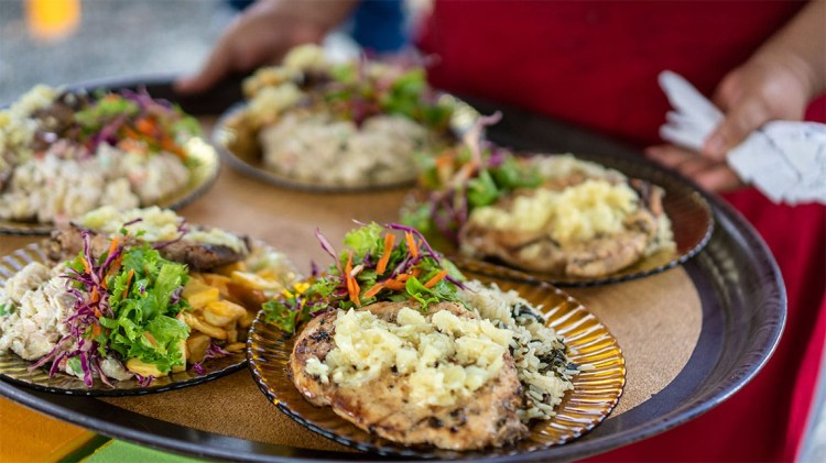 Waitress brings a plate full of traditional St Lucian food