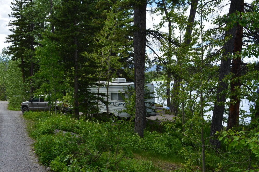 RV and pickup truck in the woods backing onto lake
