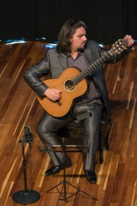 Emerson Salazar tunes his guitar for the performance