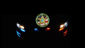Alachua County Sheriff's Office logo, at night, with patrol car lights