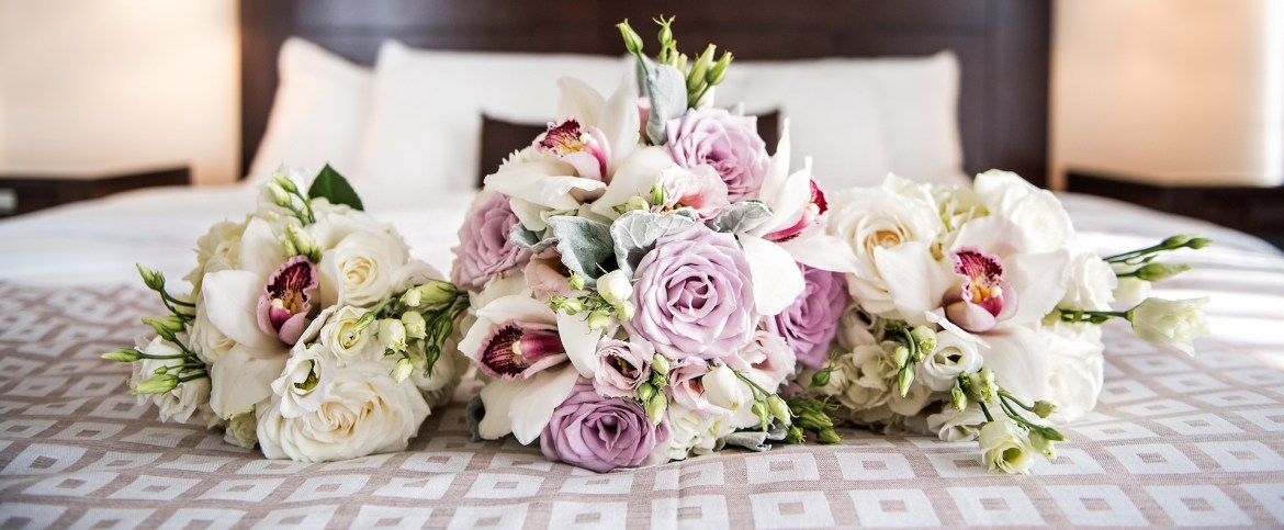 A Bouquet of blush, pink, white and pastel flowers and roses on a soft bed waiting for the bride on her wedding day. Photography by Edmonton Wedding Photographers ACS Studios.