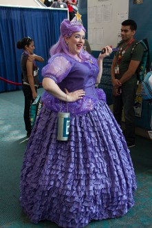 A cosplayer strikes a post in her full-length ballgown.