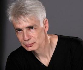 Un auteur d'une cinquantaine d'année, Pierre-François Kettler, pose de biais public, le regard noir, avec un léger sourire (grand format)