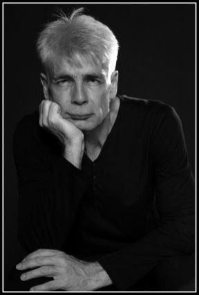 Un homme d'une cinquantaine d'années, aux cheveux blancs, Pierre-François Kettler, pose devant la photographe (moyen format N&B) (Il s'intéresse)