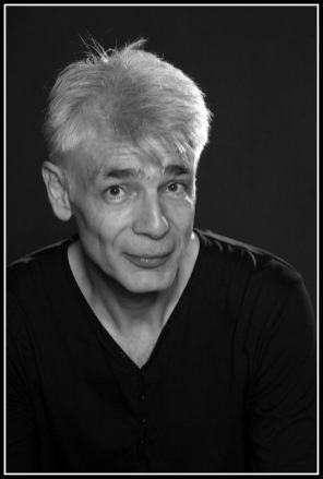 Un homme d'une cinquantaine d'années, aux cheveux blancs, Pierre-François Kettler, pose devant la photographe (moyen format N&B). (Il est dubitatif)