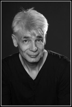 Un homme d'une cinquantaine d'années, aux cheveux blancs, Pierre-François Kettler, pose devant la photographe (moyen format N&B). (Il ne le croit pas)