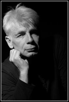Un homme d'une cinquantaine d'années, aux cheveux blancs, Pierre-François Kettler, pose devant la photographe (moyen format N&B). (Il croit se souvenir)
