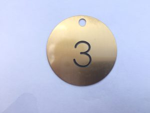 Engraved brass tag with black lettering and a drill hole for attaching