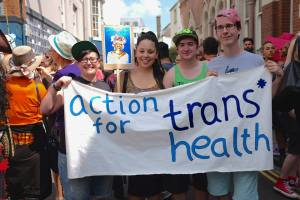 A photograph of four people smiling towards the camera and holding a hand drawn Action for Trans* Health banner infront of a crowd of people.