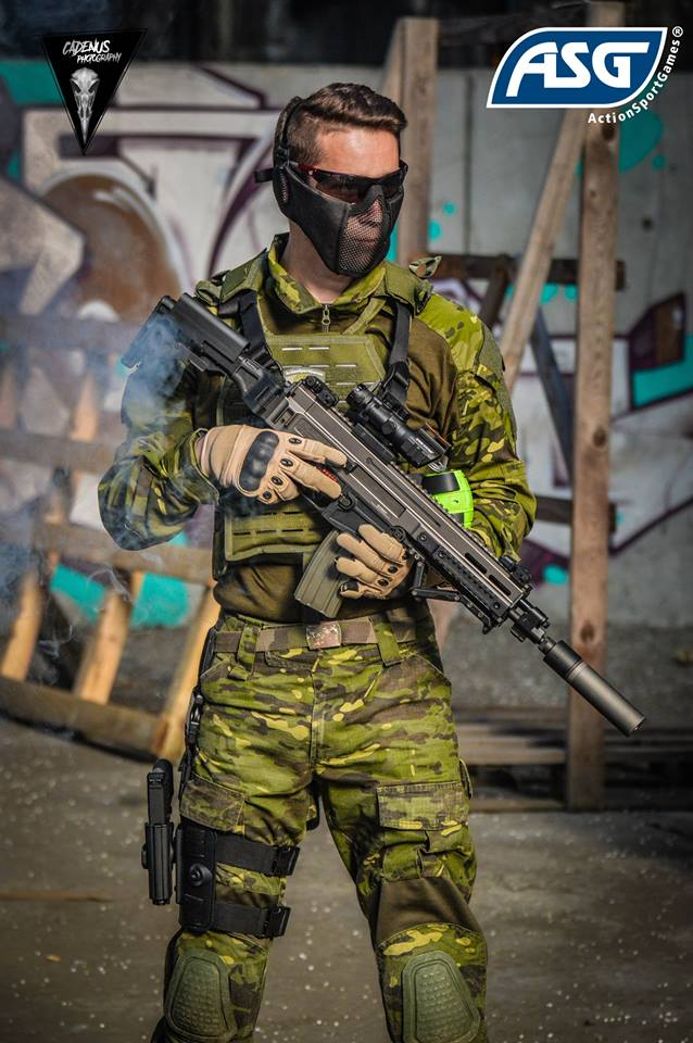 Airsofter in camo with assault rifle.