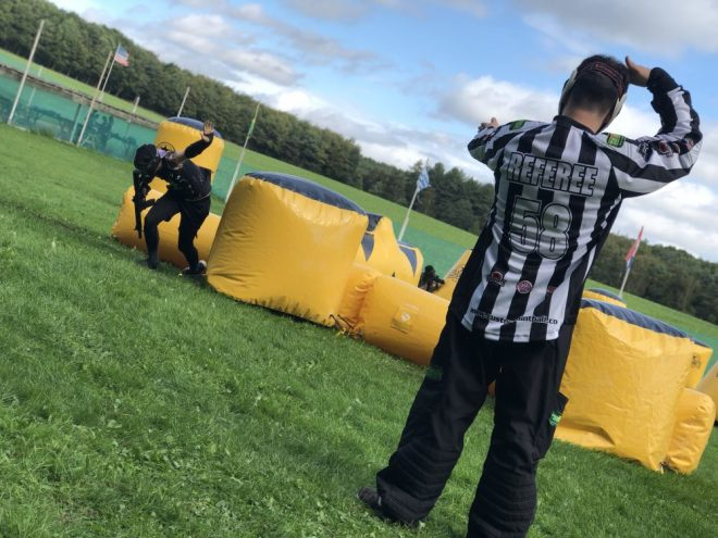 A referee calls a player hit amongst inflatable obstacles at a speedsoft event