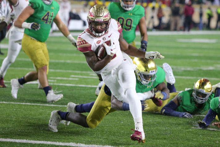 Cam Akers breaks through the Notre Dame Fighting Irish line for positive yards