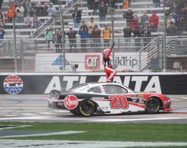 Christopher Bell jumps on the roof of his car celebrating his victor at Atlanta Motor Speedway