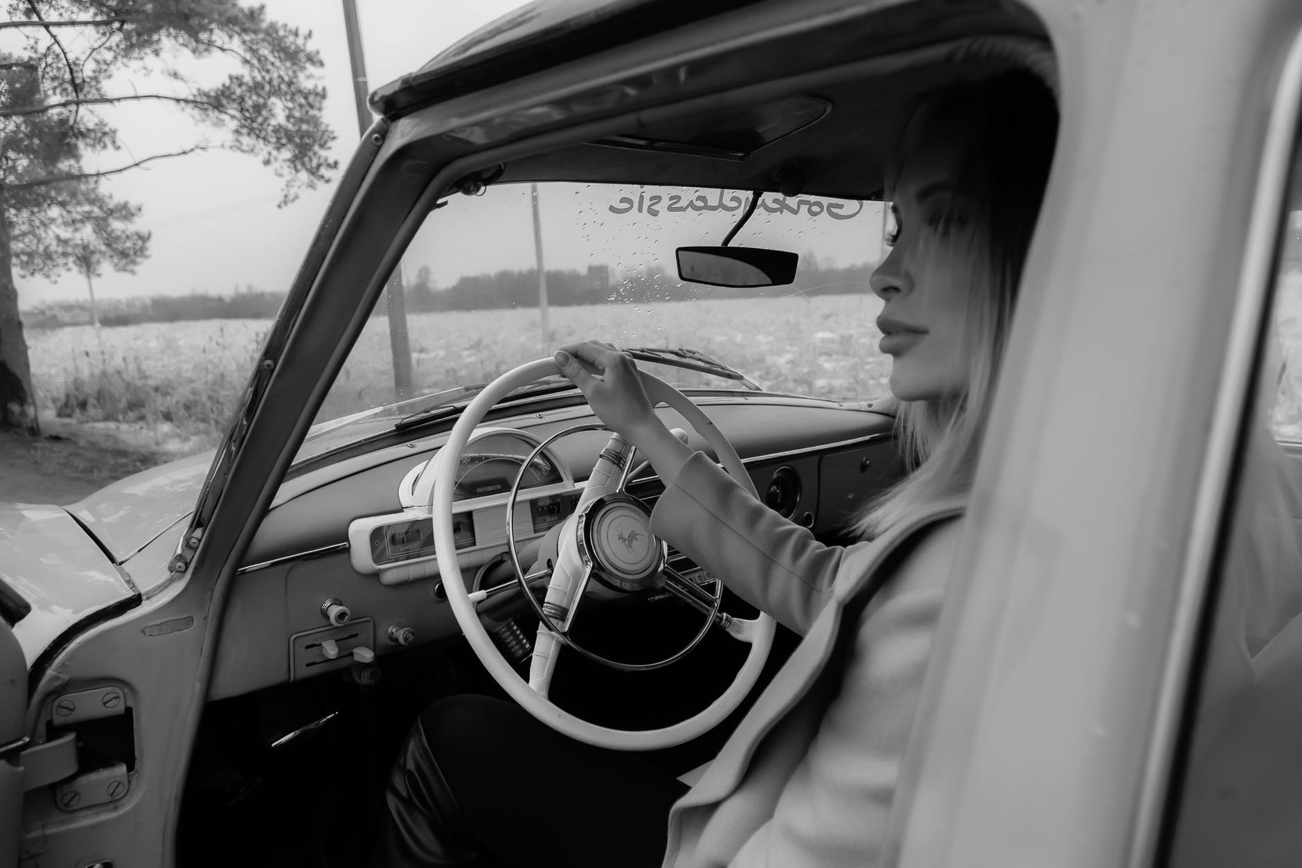 pensive female driving vintage car in daylight