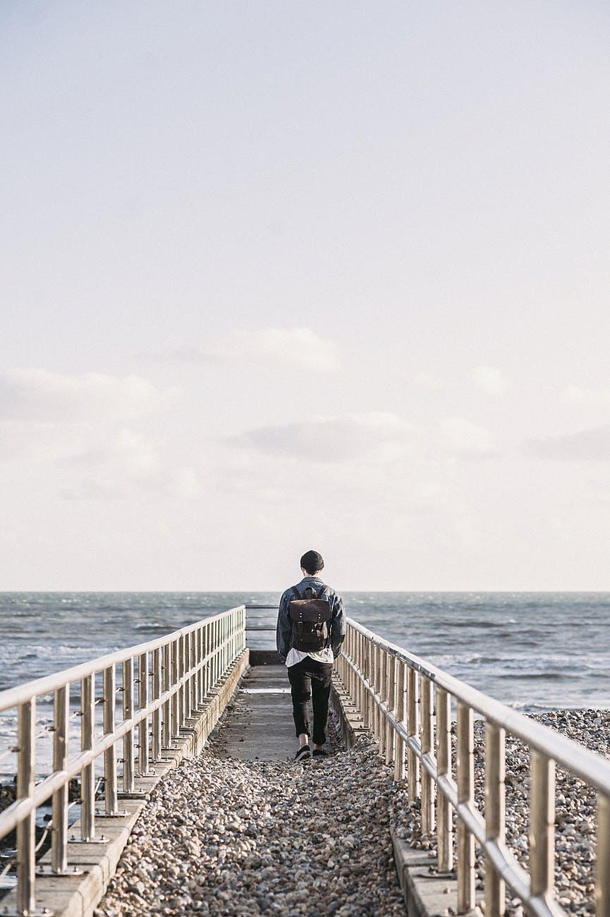man in black jacket walking on gray concrete dock