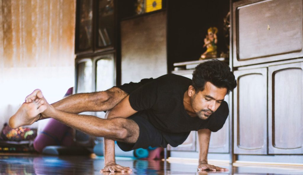 Man practising yoga at home