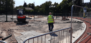 Construction site at Athltics Track with man wearing a high-visibility jacket at Paddington Recreation Ground