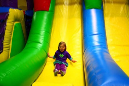 a girl enjoys the inflatable slide at planet bounce in canonsburg pennsylvania