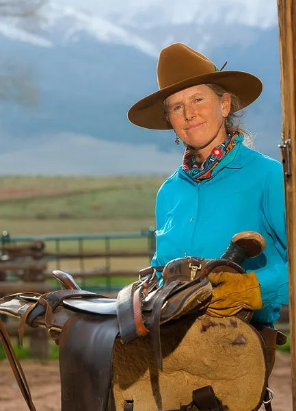 Westcliffe Colorado's Music Meadows Ranch woman owner carrying saddle back to barn