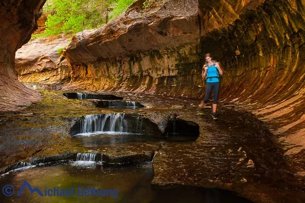 Female hiker walking by pools in the Subway section of the Left Fork of North Creek hike in Zion National Park