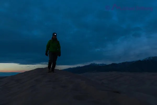hiker with headlamp at dusk on Great Sand Dunes