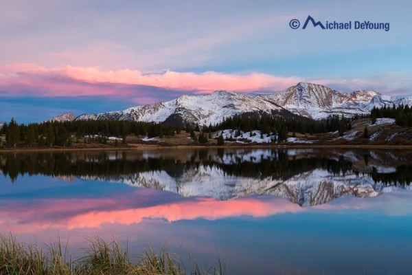 Little Molas Lake with recent snow on surrounding peaks, San Juan Mountains, Colorado on October 2, 2013, 15 minutes after sunset with glowing dense cirrus and altocumulus clouds all comprised of ice crystals which produces the pink colors.
