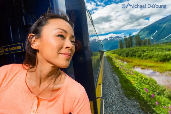 Passenger on Alaska Railroad's Glacier Express peers out window between cars traveling up the Placer River Valley toward Spencer Glacier